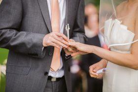 Foto del novio que le pone el anillo de bodas a la novia